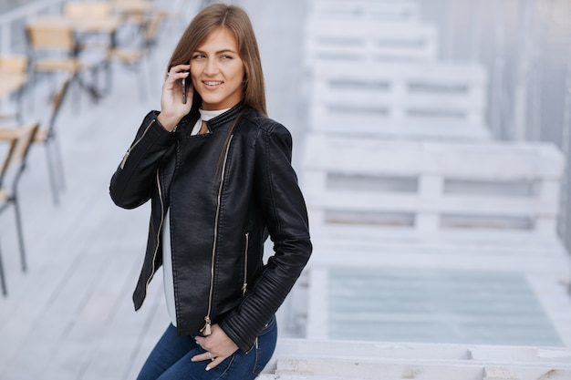 Smiling woman sitting on a white wooden board talking on the phone