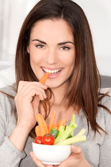 Donna sorridente sul divano a mangiare insalata di verdure