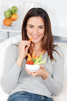 Smiling woman on sofa with vegetable salad