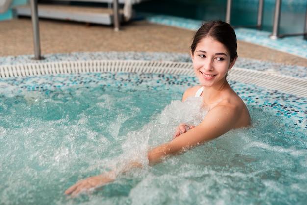 Donna sorridente nella vasca idromassaggio della spa