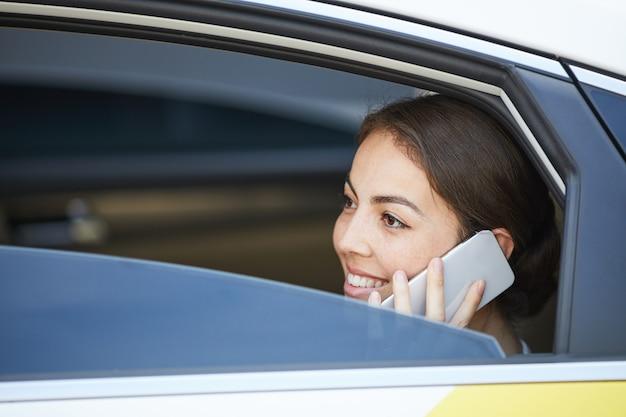 車の中で電話で話す笑顔の女性