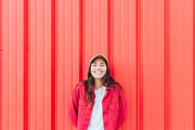 Smiling woman standing against red corrugated background