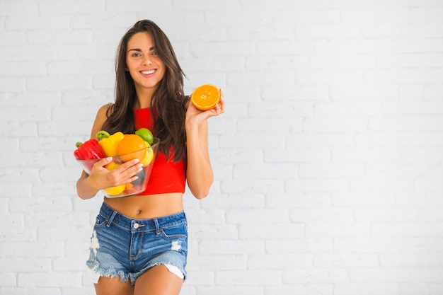 Smiling woman standing against wall holding fresh vegetable and fruits