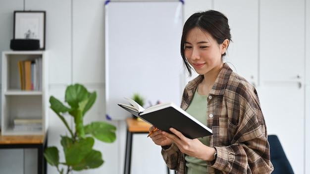 Улыбающаяся женщина, стоящая в офисе и читающая книгу.