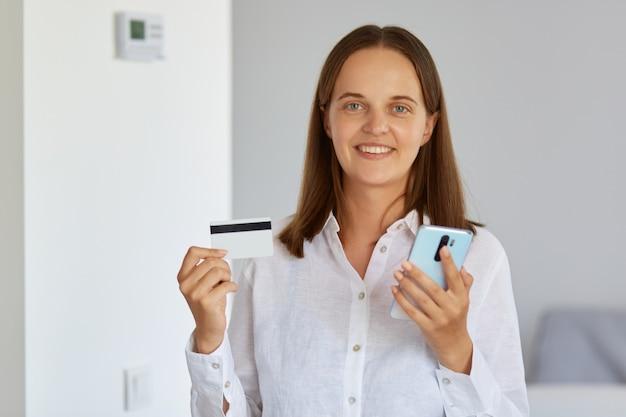 クレジットカードと携帯電話を手に、カメラを見て、ファッション店で買い物をするためのオンライン支払いをし、白いシャツを着て屋内に立っている笑顔の女性。