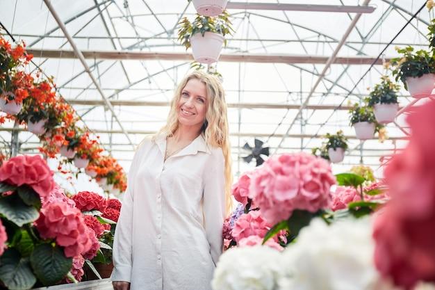 カラフルなアジサイと美しいピンクの花産業温室の近くに立っている笑顔の女性