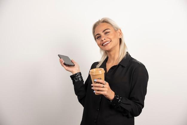 携帯電話とコーヒーのカップと一緒に立っている笑顔の女性。高品質の写真