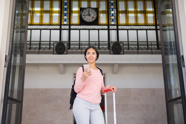 Smiling woman standing with suitcase in station hall