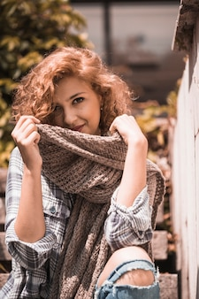 Smiling woman on steps holding scarf