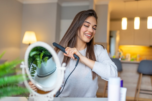 Smiling woman straightening hair in front of mirror.