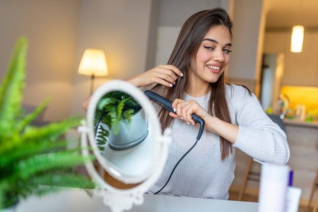 Усмехаясь женщина выправляя волосы с раскручивателем волос дома.