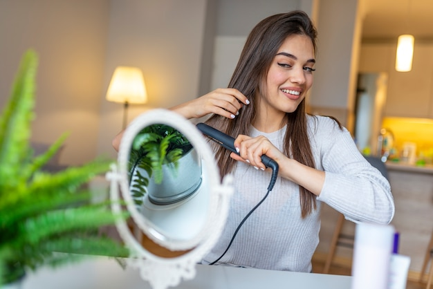 Smiling woman straightening hair with hair straightener at home.