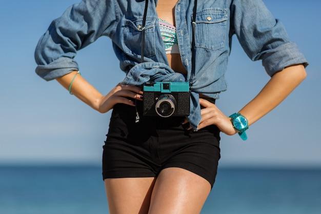 Donna sorridente in cappello di paglia e vestito estivo alla moda in posa con la retro macchina fotografica sulla spiaggia.