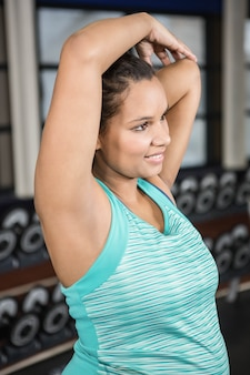 Smiling woman stretching arms in sportswear in the gym