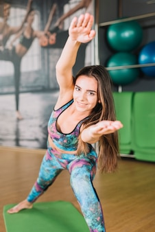 Smiling woman stretching her arms and looking at camera in gym