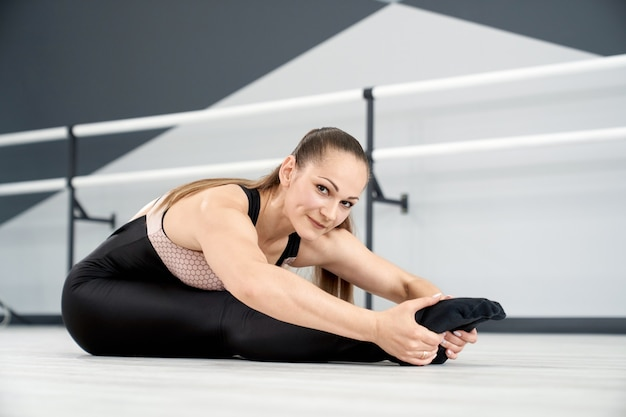 Smiling woman stretching with head on knees