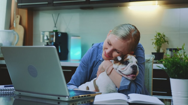 Smiling woman stroking and hugging the bulldog while sitting at the computer
