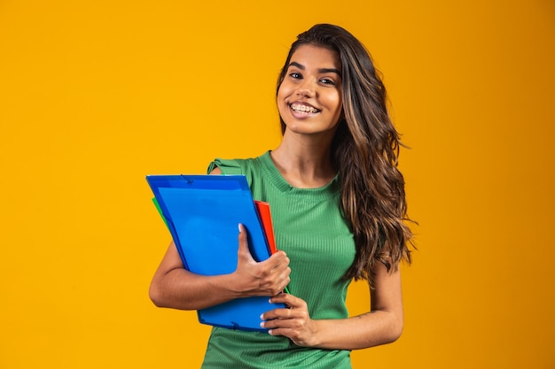 Smiling woman student with school books in hands on yellow background.