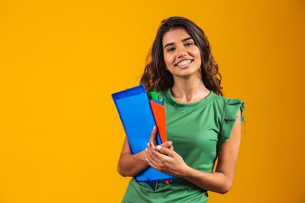 黄色の背景に手に教科書と笑顔の女子学生。