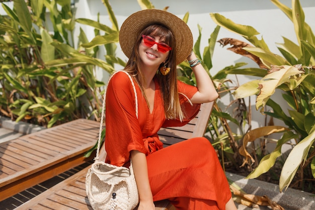 Smiling woman in stylish orange outfit and straw hat chilling on deck chair near pool.
