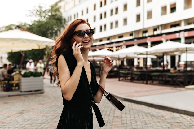 Donna sorridente in occhiali da sole e colloqui di vestito sul telefono