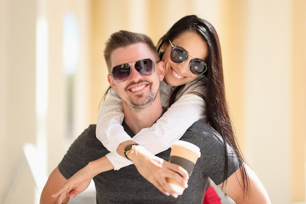 Smiling woman in sunglasses holds coffee and hugs man