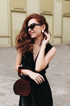La donna sorridente in occhiali da sole tiene la borsa alla moda