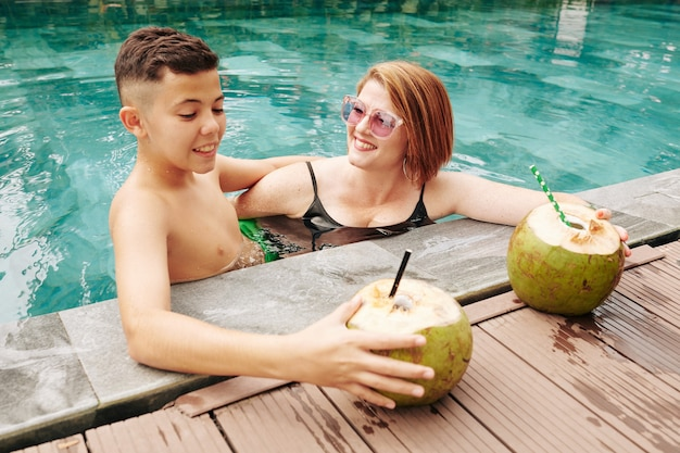 Smiling woman in sunglasses looking at happy kid when they are spending time in swimming pool and drinking coconut cocktails