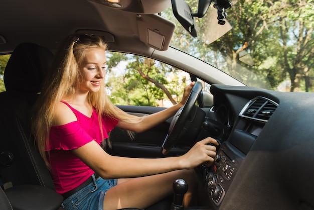 笑顔の女性がキーが付いている車のスイッチ