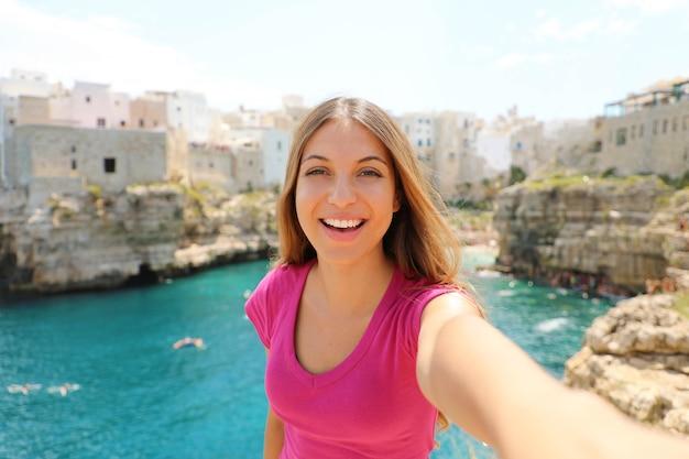 Улыбающаяся женщина делает селфи в полиньяно кобыла, средиземное море, италия