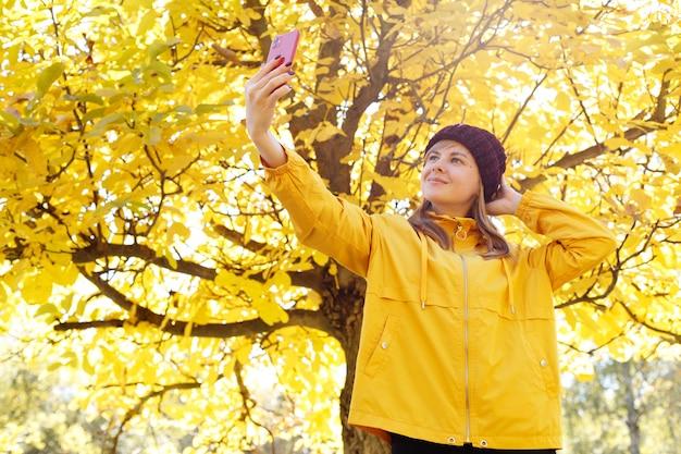 笑顔の女性が秋の紅葉を背景に自撮り