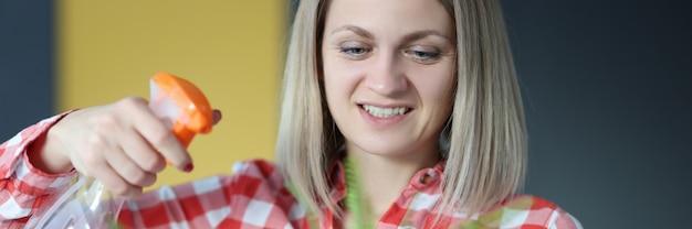 笑顔の女性が植木鉢で家の花の世話をします。家の植物の概念