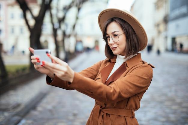秋の日の外で彼女の電話で写真を撮って笑顔の女性