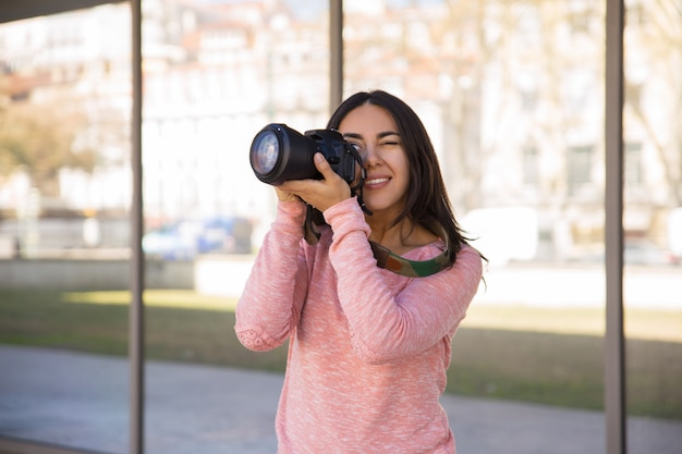 Smiling woman taking photos with camera outdoors
