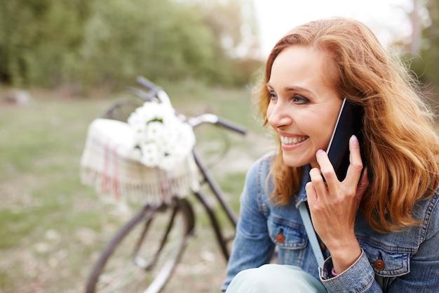 Улыбающаяся женщина разговаривает по мобильному телефону