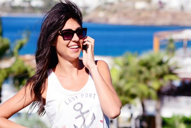 Sorridente donna che parla sul suo telefono