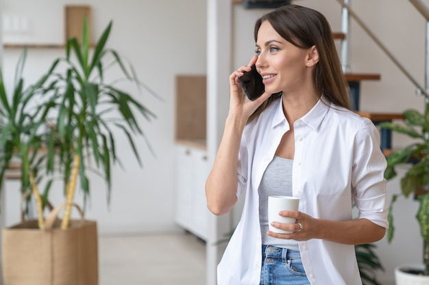 Smiling woman talking on mobile phone looking away holding white mug drinking coffee or tea at home.