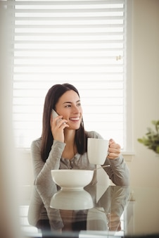 Smiling woman talking on mobile phone while eating breakfast