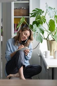 Улыбающаяся женщина разговаривает по мобильному телефону, пишет в блокноте, сидя у окна дома.