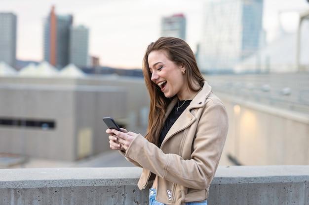 彼女の携帯電話で話している笑顔の女性