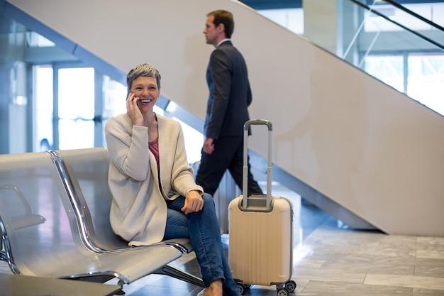 Улыбающаяся женщина разговаривает по мобильному телефону в зоне ожидания