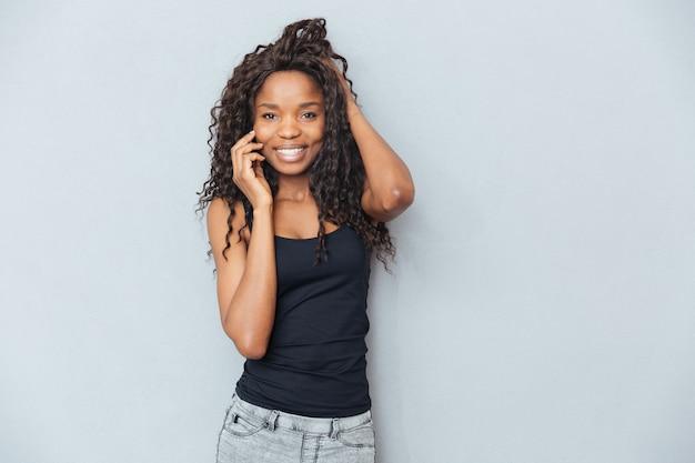 Улыбающаяся женщина разговаривает по телефону над серой стеной
