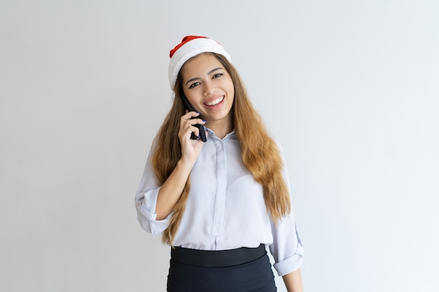 Smiling woman talking on smartphone and wearing santa claus hat