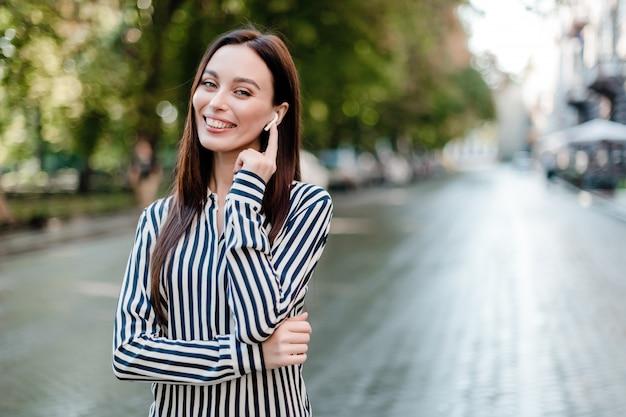 Smiling woman talking through wireless earpods outdoors