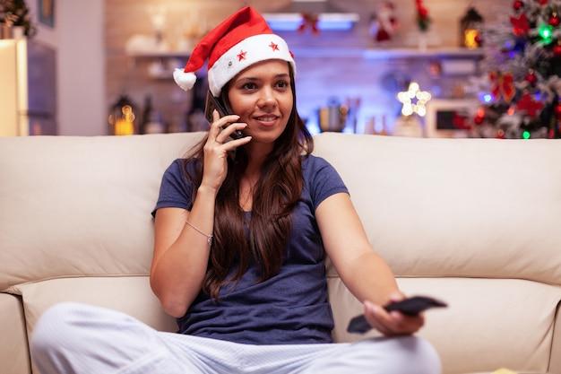 Улыбающаяся женщина разговаривает с другом по телефону, смотря расслабляющий рождественский фильм