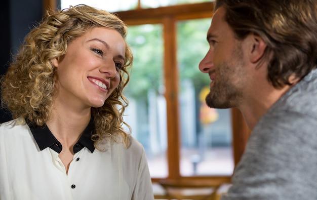 コーヒーショップで男性と話している笑顔の女性