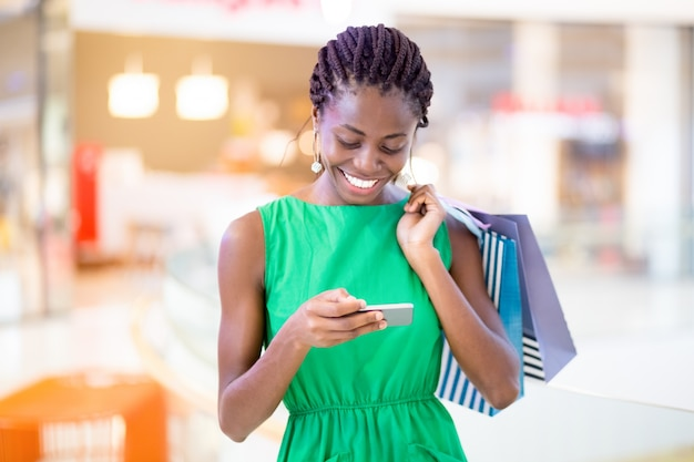 Smiling woman texting message in shopping mall