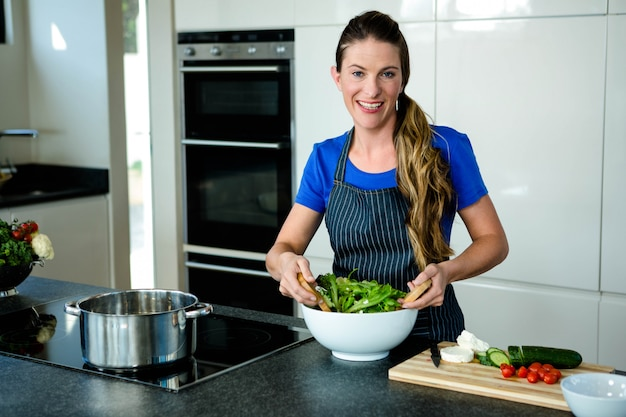 Smiling woman tossing a salad in the kitchen