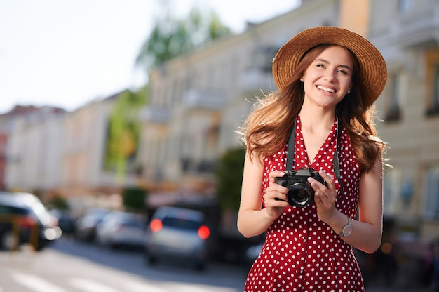 Smiling woman tourist in straw hat with camera walks in the summer city