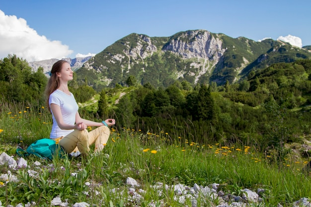 Smiling woman tourist with closed eyes sitting in yoga lotus pose on grass in a alpine mountains